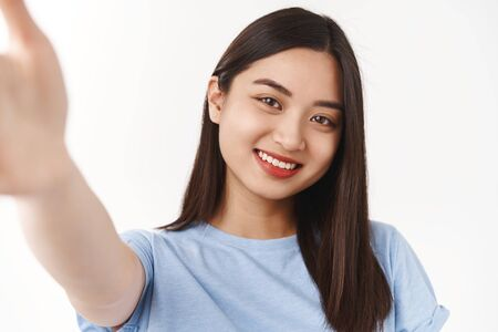 Authentic body-positive shot asian cute tender happy girl extend hand hold camera taking selfie smartphone smiling cheerful express positive upbeat mood have acne prone skin, forehead pimples