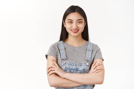 Girl feels like pro. Attractive self-assured asian woman freelance student hold arms crossed body smiling determined motivated receive first prize ready win grinning pleased white background