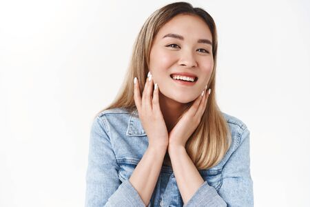 Beauty, skincare, wellbeing, diversity concept. Attractive cheerful tender young asian blond girl take care skin touch face delighted feel soft gentle cheeks smiling broadly enjoy cosmetics product Фото со стока