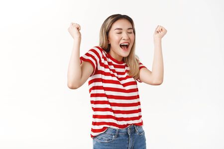 Hooray sweet success. Cheerful silly cute asian korean blond girl raising fists festive celebrating awesome good news lucky winner triumphing dancing closed eyes delighted feel taste victory