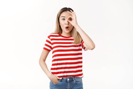 Wondered amused emotive blond asian woman drop jaw folding lips wow sound stare camera excited amazed show okay ok monocle gesture astonished look through fingers white background Фото со стока