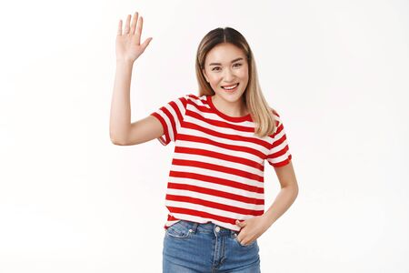 Hey friends how hanging. Friendly outgoing sociable cute asian blond girl raise hand waving palm hi hello gesture smiling broadly happy introduce herself new members, standing white background