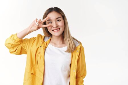 Motivated charismatic cute asian blond girl aim victory show peace disco sign eye smiling broadly, easygoing female student having fun enjoy awesome summer day wish happy pride Фото со стока