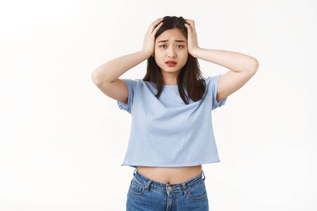 Gosh what should I do. Perplexed panicking young tired asian female student grab head panic confusion helpless situation worry how deal problems standing puzzled frustrated white wall