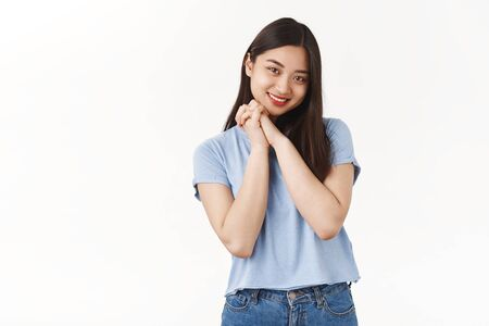 Tender cheerful lovely young asian girl clench palms together touched amazed tilt head smiling cute look heartwarming nice scene grinning melting heart stand white background impressed