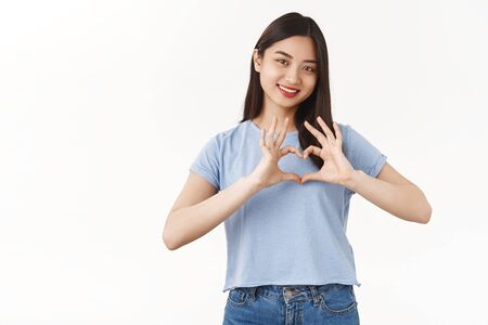 Girl confess true feelings love girlfriend. Tender cute brunette asian woman show heart gesture tilt head smiling silly romantic cheerful mood happy be healthy relationship white background