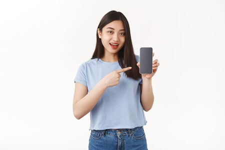 Optimistic good-looking asian girl dark hair introduce app hold smartphone pointing cellphone screen speaking about interesting application game stand white background show social media profile Фото со стока