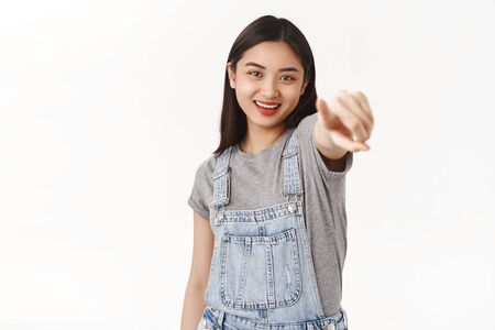 Girl picking you made choice. Confident good-looking asian woman pointing camera index finger smiling entertained laughing over funny lama stand white background amused cheerful