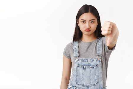 Ignorant displeased whining silly teenage asian girl disliking present sulking offended disappointed show thumb down dismay reluctance uninterested boring party standing white background upset