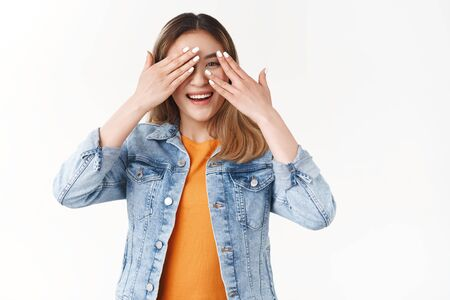 Girl eager see present cannot hold anticipation tempting check out cover eyes peeking through fingers joyful waiitng surprise-gift standing white background smiling broadly toothy happy grin Фото со стока