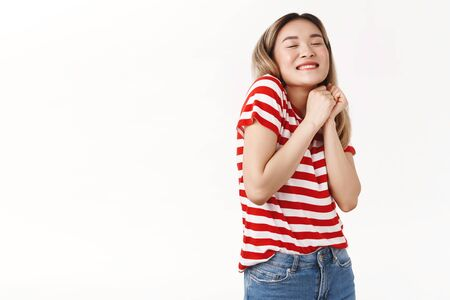 Cheerful cute silly blond asian girl clench hands together lovely dreamy close eyes smiling squeez arms delighted imaging romantic tender moment rejoicing happily, standing white background excited