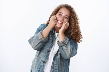 Happy charismatic tender silly chubby cute girl touching cheeks smiling cheerfully have best day enjoy life having fun doing good standing white background denim jacket fool around mimicking Banco de Imagens