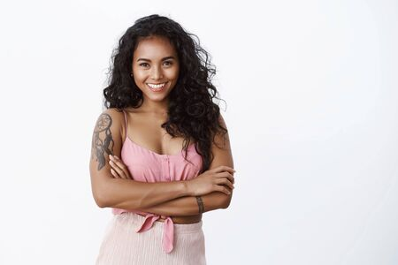 Waist-up shot successful happy elegant african-american curly-haired woman with tattooed arms, cross hands chest and smiling toothy, looking confident and encouraged, white background