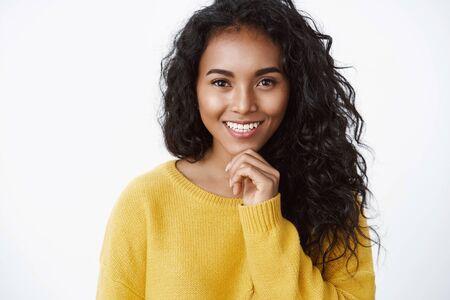 Concept d'émotions, de bonheur et de beauté. Jolie femme aux cheveux bouclés en pull jaune souriante ravie, comme ce qu'elle considère comme un bon choix, touche le menton réfléchi, réfléchit à une bonne idée