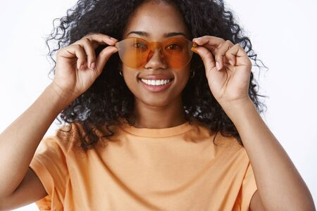 Close-up charming smiling african american girl afro hairstyle checking sunglasses bying new pair glasses get ready tourist travel vacation smiling delighted picking eyewear store, white background Stock fotó
