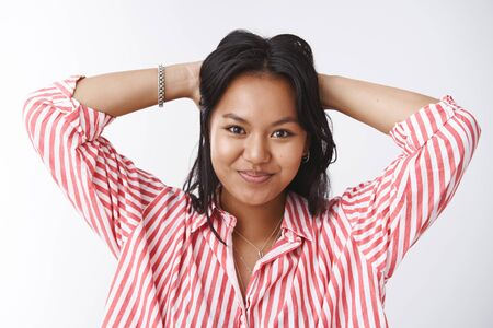 No work today, time be lazy. Energized good-looking happy young polynesian female student in striped blouse holding hands behind head relaxed and smiling confident at camera over white wall