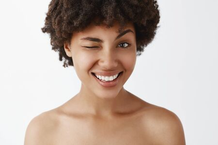 Close-up shot of emotive happy and friendly-looking attractive dark-skinned model with afro hairstyle posing naked, smiling broadly and winking as if hinting on some interesting concept or secret