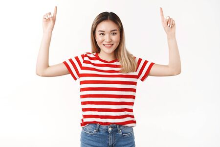You regret not see this. Confident assertive joyful lucky blond asian girl willing you check-out amazing new promo special raise index fingers pointing up smiling toothy self-assured advertising Stock Photo