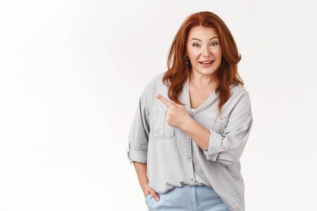 Good-looking redhead stylish middle-aged woman wearing trendy blouse lively pointing upper left corner awesome interesting sale promo recommend click link try out product smiling camera Stok Fotoğraf - 130173960