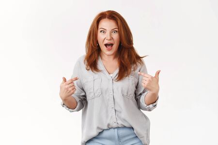 Who me. Amazed speechless impressed middle-aged pretty redhead woman surprised win lottery pointing herself shocked open mouth drop jaw astonished receive unexpected excellent offer