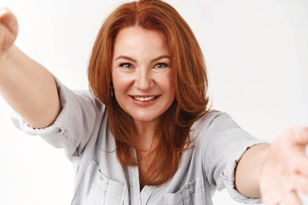 Joyful successful stylish redhead middle-aged beautiful woman taking selfie hold camera both hands smiling toothy delighted taking perfect shot proud how she looks standing white background