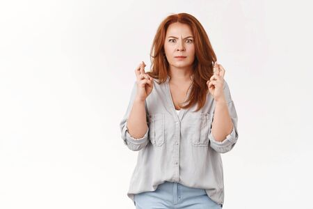 Pressured worried middle-aged intense ginger woman frowning distressed cross fingers good luck popped eyes camera stare supplicating make wish come true hopefully awaiting positive results lottery