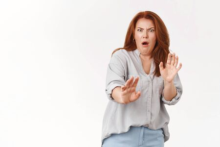Oh gosh take away from me. Cringing displeased redhead middle-aged woman show aversion step back reluctant raise hands defensive grimacing displeased awful terrible smell, white background