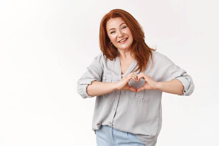 Family in her heart. Tender joyful charismatic middle-aged 50s redhead elegant woman smiling delighted happiness show love sign chest express sympathy cherish relationship, standing white background Foto de archivo