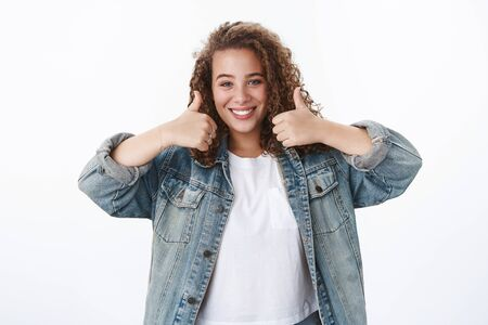 Supportive girlfriend blue eyes curly-haired wearing denim jacket show support cheering friend give positive recommendation thumbs-up liking awesome outfit grinning satisfied, white background