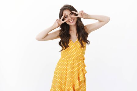 Positive lovely european woman with tattoos wear feminine light summer dress, tilt head tender smile and show peace, victory signs over eyes, stand white background, send joyful cheering vibes