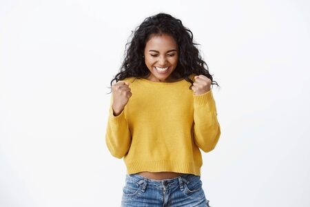 Lucky excited attractive dark-skinned girl in yellow sweater celebrating, fist pump and smiling with closed eyes, thank god for amazing opportunity, got promotion, cheering, stand white background