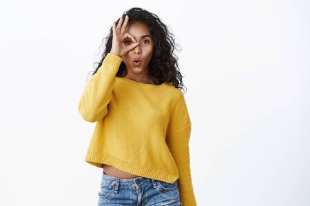 Curious amused young cute african-american girl in yellow sweater folding lips gasping astonished say wow, hold okay circle fingers over eye and gazing through, check-out interesting offer