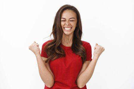 Girl feeling accomplish finally achieve goal. Happy triumphing cute brunette woman fist pump, smiling joyful with closed eyes celebrating success, winning competition, standing white background 版權商用圖片 - 132011543