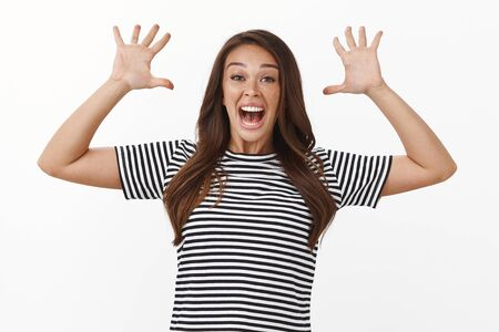 Playful carefree funny woman jump out of nowhere to scare and prank friend, making jazz hands and smiling broadly, laughing fooling around, grimacing goofy expressions, white background
