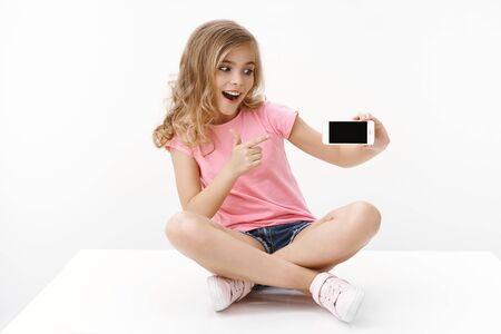 Cheerful excited cute blond little girl sitting on floor with crossed legs, hold smartphone, pointing mobile phone display and looking thrilled cellphone surprised, showing favorite internet page