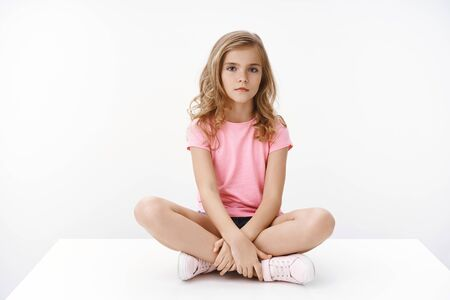 Serious indifferent cute blond little girl sitting on floor, legs crossed, look bored and unamused, boring homesick, unwilling do homework, pose white background in pink t-shirt and shorts