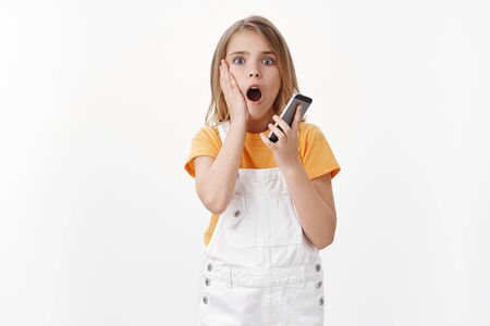 Shocked cute blond little girl finished call, hold smartphone, drop jaw gasping amazed, touch cheek impressed, stare camera fascinated, found out amazing news, stand white background Фото со стока - 132012040
