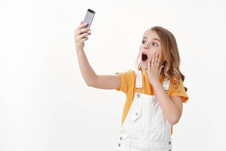Cute charismatic little caucasian girl, child playing with smartphone making funny playful grimace, extend arm hold mobile phone taking selfie with surprised amazed emotion, white background