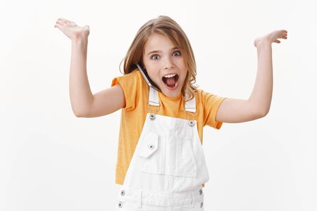 Silly pretty energized cute blond little kid, girl shrugging raise hands up, hold mobile phone on shoulder, talking with friend via smartphone, smiling amused, showing focus open mouth fascinated
