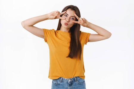 Fille caucasienne féminine idiote et ludique en t-shirt jaune, tête inclinée pliant les lèvres dans un baiser, mwah, montrant un signe de paix ou de victoire près des yeux, profitez d'une fête géniale, s'amuser, se sentir enjouée et émotive
