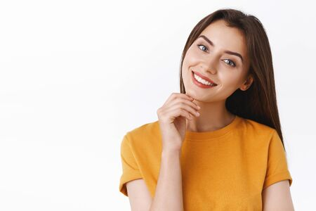 Tenderness, beauty and women concept. Sassy coquettish caucasian girl in yellow t-shirt, tilt head and smiling joyfully, touching chin gently, express sensuality and upbeat emotion, white background Stok Fotoğraf