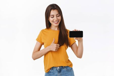 Girl fully satisfied with awesome new mobile application, recommend everyone download. Pleased good-looking woman in yellow t-shirt, holding smartphone horizontally, showing thumbs-up