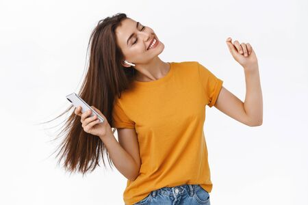Girl whip her hair back and forth as enjoying awesome sound of wireless earphones, holding smartphone, close eyes relaxed and carefree dancing to rhythm of music, white background 写真素材