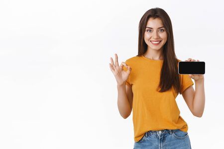 Assertive good-looking brunete woman recommend application or game, showing her score smartphone display, holding mobile phone horizontally, smiling satisfied make okay, approval gesture