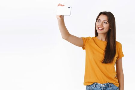 Confident, carefree attractive brunette girl in yellow t-shirt, raising smartphone horizontally, smiling at mobile display, taking selfie, posing near white background, express joy