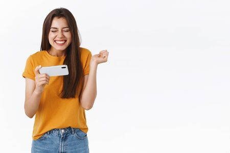 Cheerful cute modern girl triumphing as pass level in game, bit friends score in mobile app, holding smartphone horizontally, smiling with closed eyes excited clench fist, white background