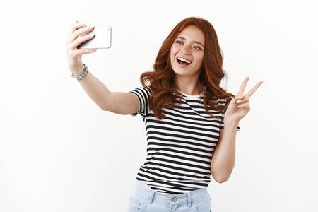 Cute carefree redhead female in striped t-shirt enjoy youth and holidays, extend arm taking selfie using smartphone, showing peace, victory sign goodwill, smiling upbeat, white background