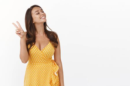 Enthusiastic carefree brunette girl feeling happiness, enjoy summer vacation, travelling abroad seaside wear yellow cute dress, show victory or peace sign in goodwill raise head joyfully, smiling Stock Photo