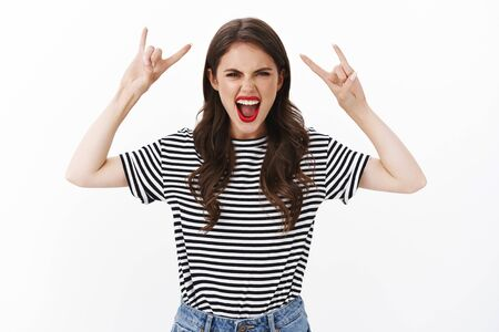 Rebellious enthusiastic cool stylish woman raise hands up, show rock-n-roll, heavy metal sign yelling entertained carefree enjoy awesome concert, party all night, stand excited white background