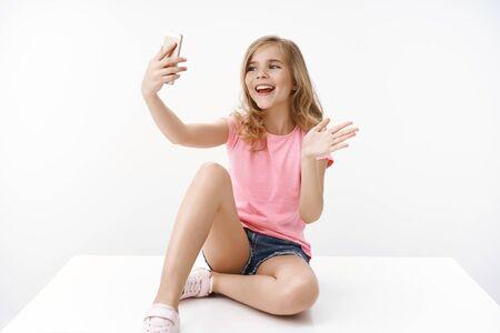 Fröhliche, enthusiastische, glückliche, blonde Teenager-Mädchen, die gekreuzte Beine auf dem Boden sitzen, Smartphone halten, Blog aufzeichnen, Vater im Ausland kommunizieren, Selfie machen, Handgruß winken, sagen hallo Handy